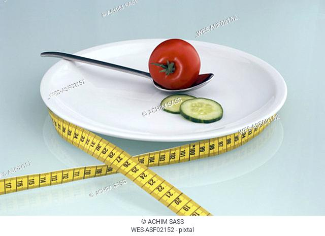 Tomato and cucumber slice on plate with measuring tape