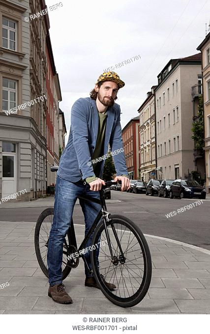 Germany, Bavaria, Munich, young man wearing basecap standing on pavement with his racing cycle