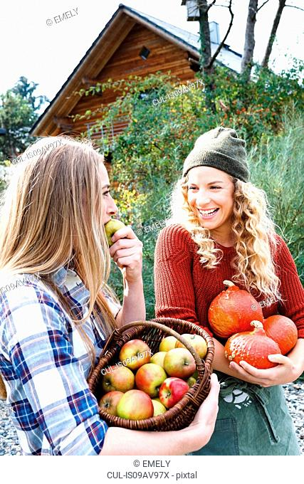 Two friends carrying homegrown produce, one woman eating apple