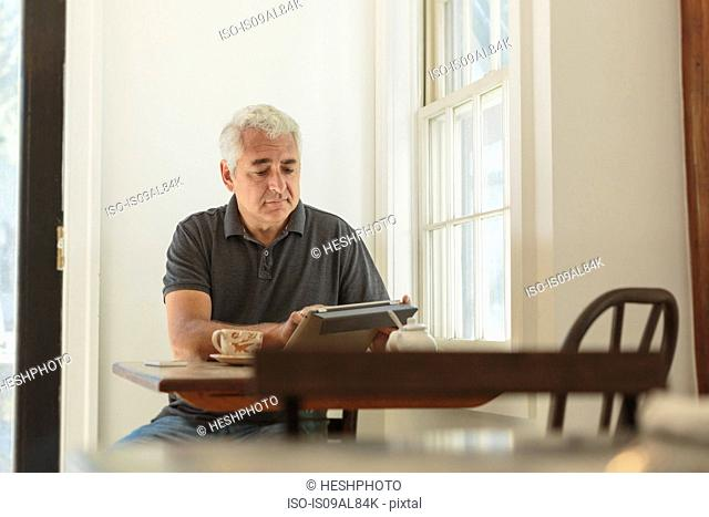 Mature man using digital tablet in country store cafe