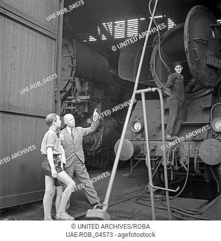 Zwei Jungen bestaunen im Bahnbetriebswerk Hamburg die Kesselreinigung einer Dampflokomotive der Baureihe 03 auf der Drehscheibe in einem Ringlokschuppen