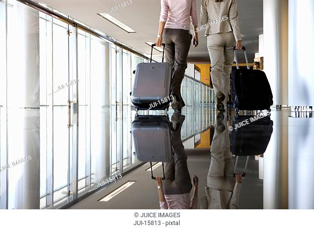 Two businesswomen pulling suitcases