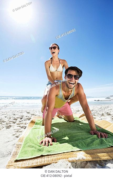 Enthusiastic couple piggybacking on beach