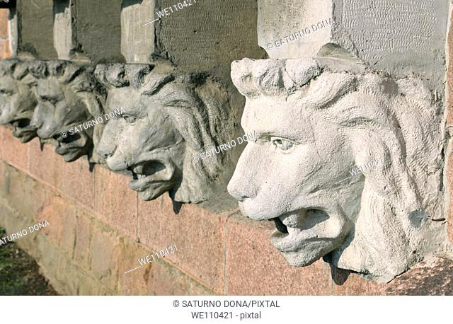 Stone lions' heads in a row