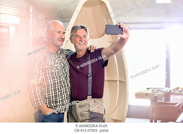 Proud, smiling male carpenters with camera phone taking selfie next too wood boat in workshop