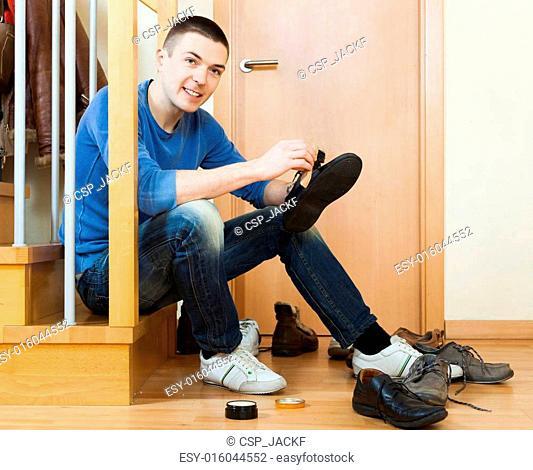 man cleaning footwear