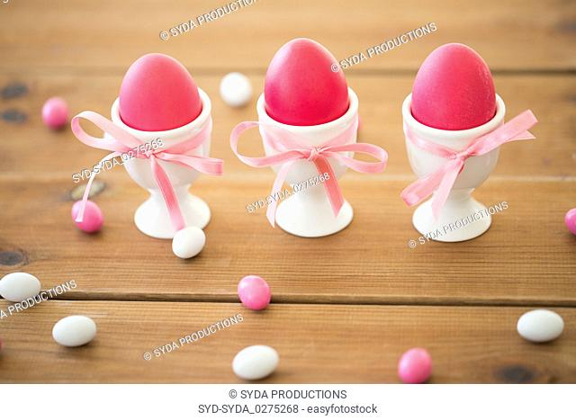 easter eggs in holders and candy drops on table
