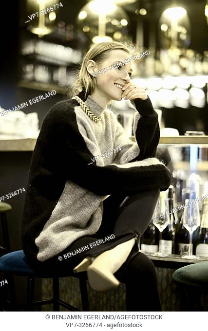fashionable blogger woman indoors at bar, in Munich, Germany