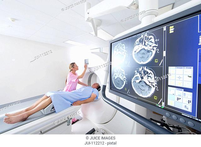 Technician nurse and patient starting CT scan in hospital behind digital brain scan