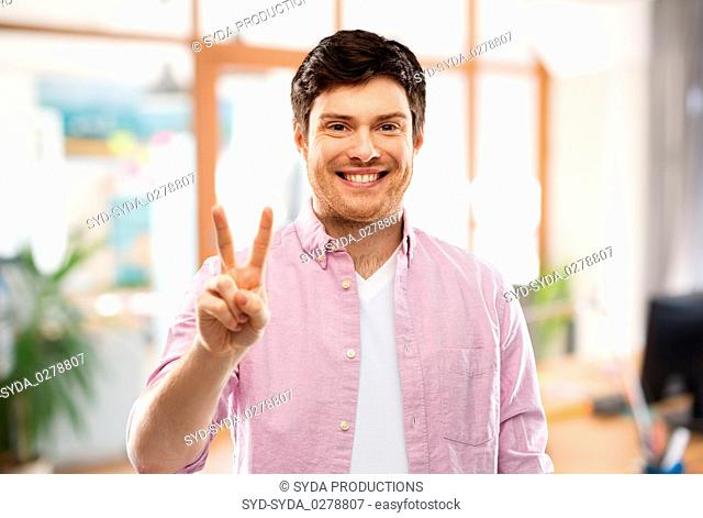 man showing two fingers or peace over office room