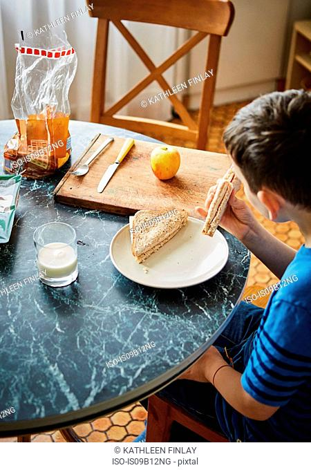 Boy at dining table eating sandwich