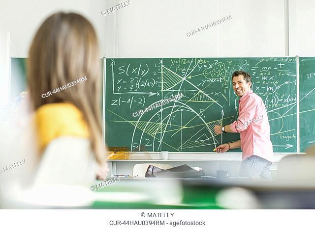 Teacher writing on board in classroom