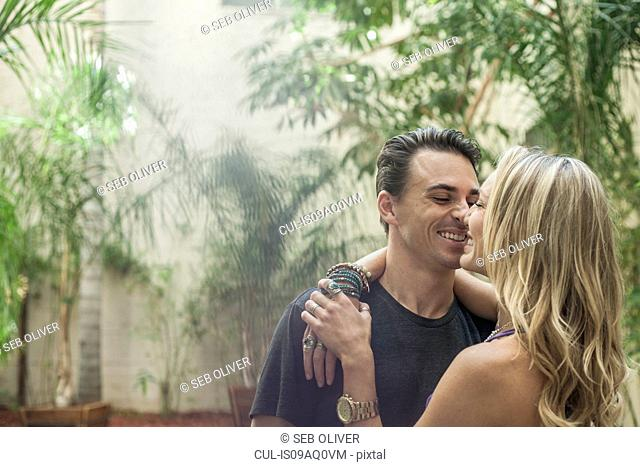 Young romantic couple, face to face, smiling, outdoors