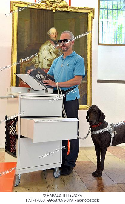 Blind Karl Kohlhaas touches a relief from the 'Blind Kit' trolley next to guide dog Angelo at the city museum 'Simeonstift' in Trier, Germany, 1 June 2017