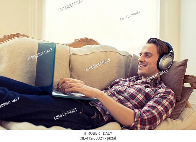 Man with headphones using laptop on living room sofa