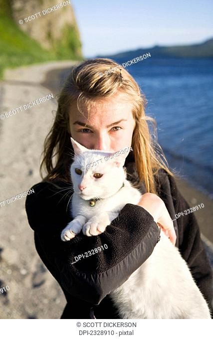 A Girl Holding Her White Cat On The Beach; False Pass, Alaska, United States Of America