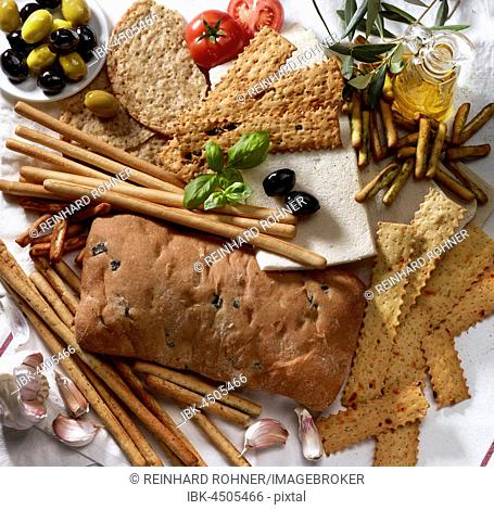 Various Italian baked goods with decoration of olive branches, green and black olives, jug of olive oil, basil, tomato and garlic