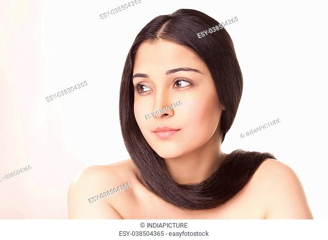 Portrait of beautiful young woman with long hair wrapped around neck