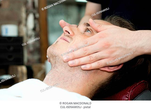 Side view of young mans head and shoulders having facial massage