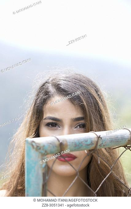 Sad young woman standing behind a metal gate
