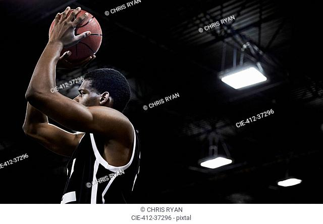 Focused young male basketball player shooting the ball in gymnasium