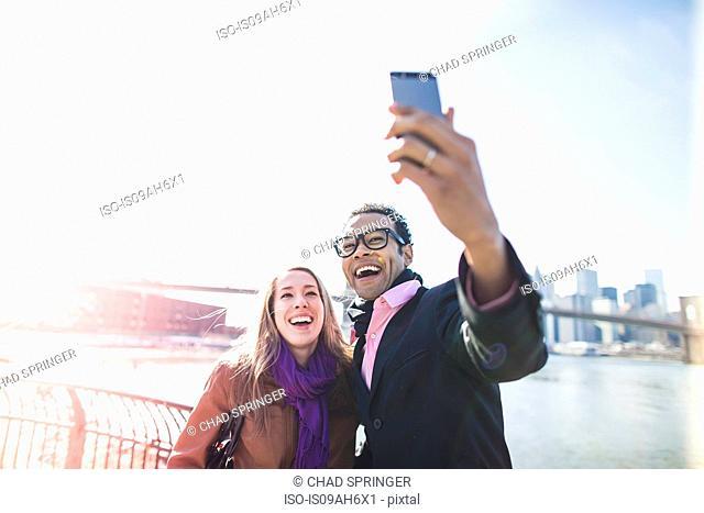 Young couple taking selfie with Brooklyn Bridge, New York, USA
