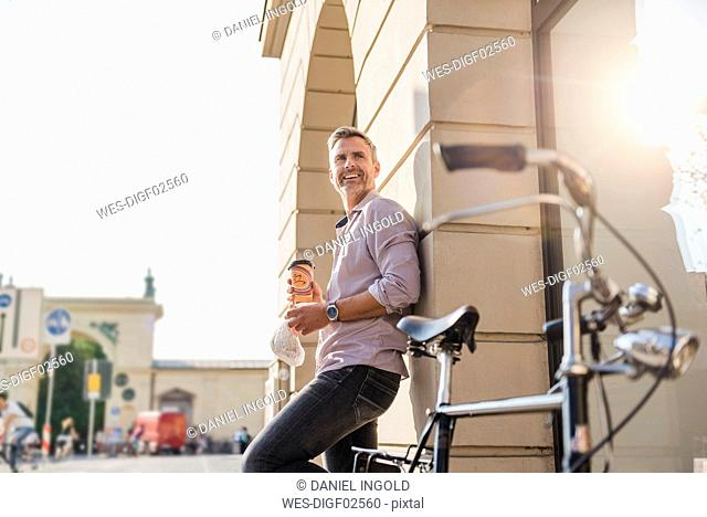 Smiling man with bicycle and takeaway coffee in the city