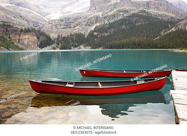 Bright red canoes on a tranquil alpine lake