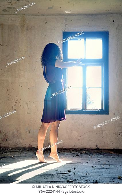 Young woman standing by the window reaching for the light