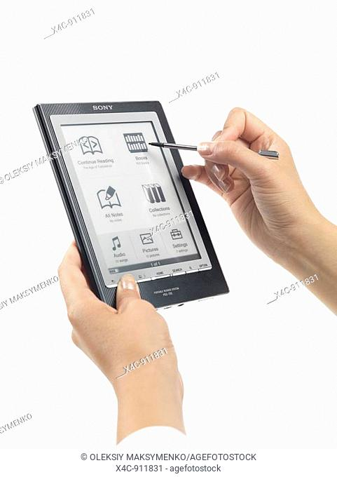 Woman using Sony Reader  PRS-700 Portable Reader System  Touch screen e-book device  Isolated on white background