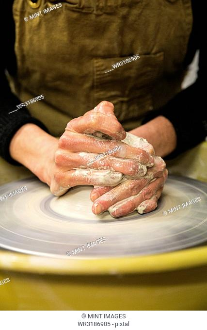 Close up of potter wearing apron working on pottery wheel, shaping clay