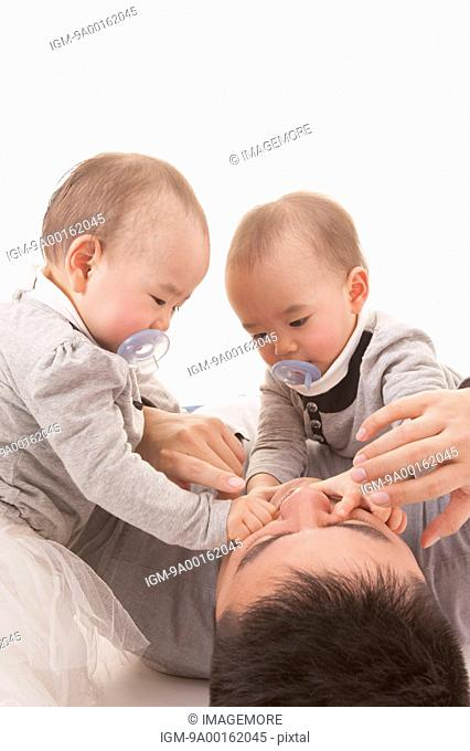 Baby twins playing with young father and looking down