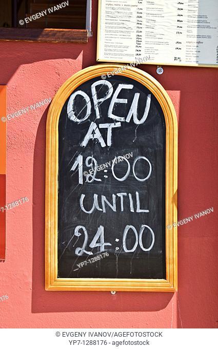 Restaurant board with open hours of restaurant, Crete, Greece