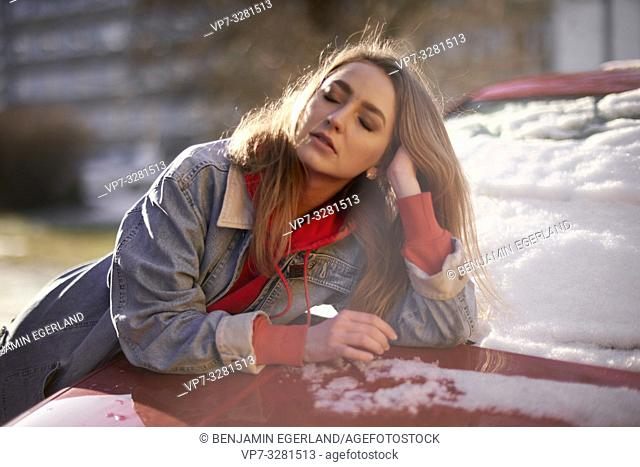 young woman leaning on car outdoors, winter seasons, in Cottbus, Brandenburg, Germany