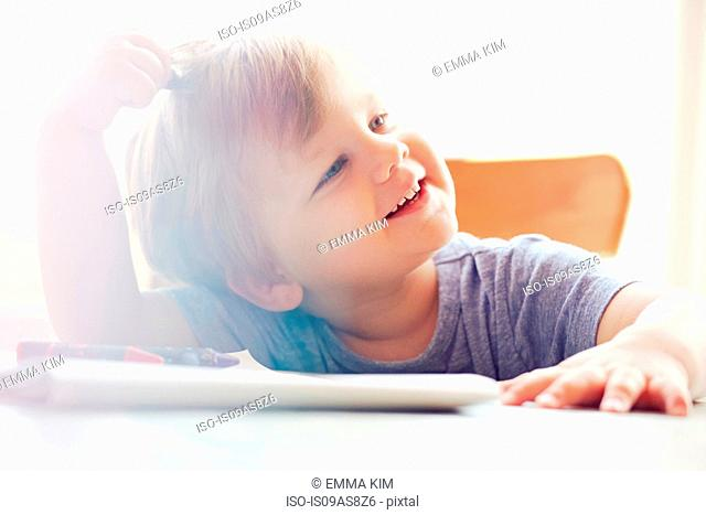 Boy sitting at table scratching head, looking away smiling