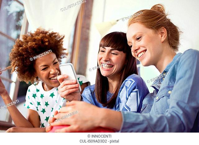 Three female friends using smartphone