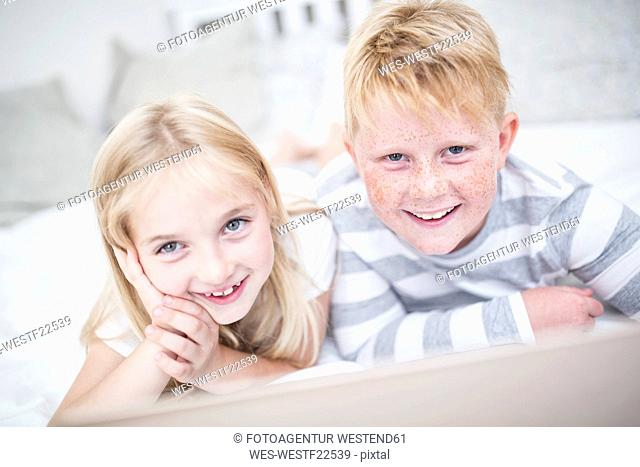Portait of smiling brother and sister lying in bed with laptop