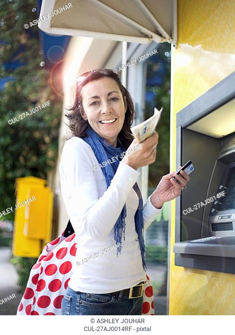 Woman getting money from cash machine