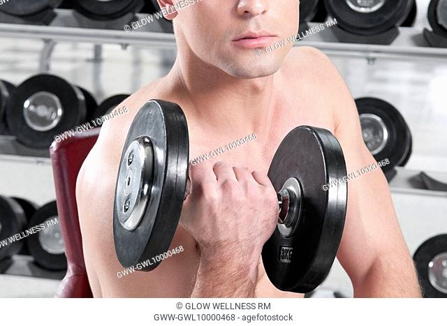 Man exercising with dumbbells in a gym