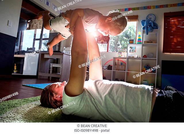 Father lying on floor, lifting baby boy in air