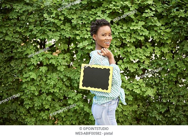 Portrait of smiling young woman with chalkboard
