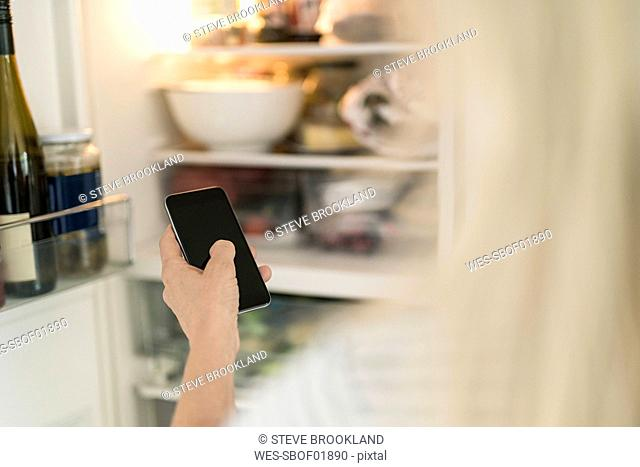 Hand of woman with smartphone checking fridge in kitchen at smart home