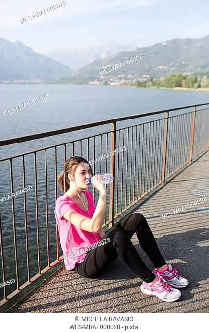 Italy, Lecco, sportive young woman drinking water after running at lakeshore