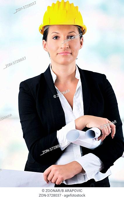 b78e5f20f24 young architect woman in business suit portrait with yellow hemet and  blueprints