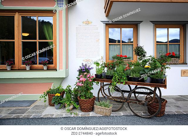 An old wooden wagon decorated with flowers. Hotel Gut Steinbach. Reit im Winkl. Upper Bavaria. Germany