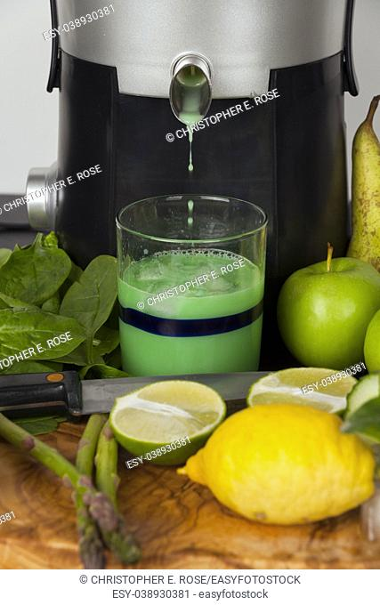 A juicer pouring fruit and vegetable juice into a drinking glass on a kitchen worktop