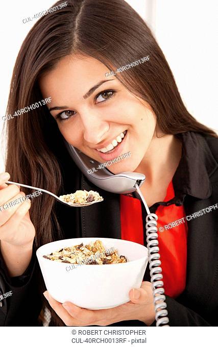 Businesswoman eating on telephone
