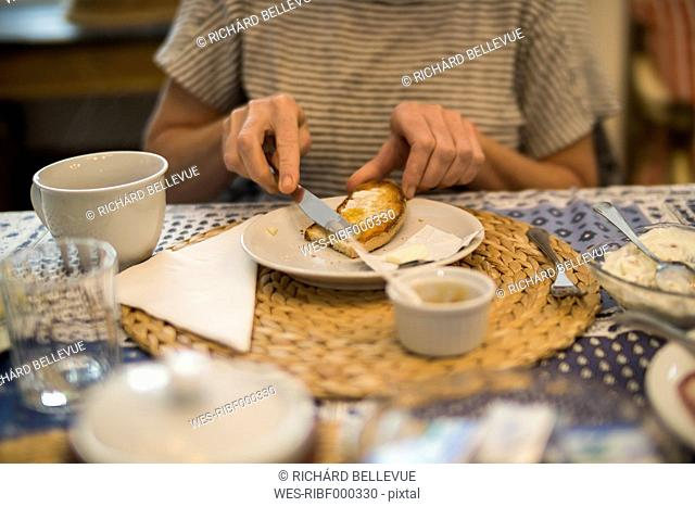 Woman spreading bread with jam