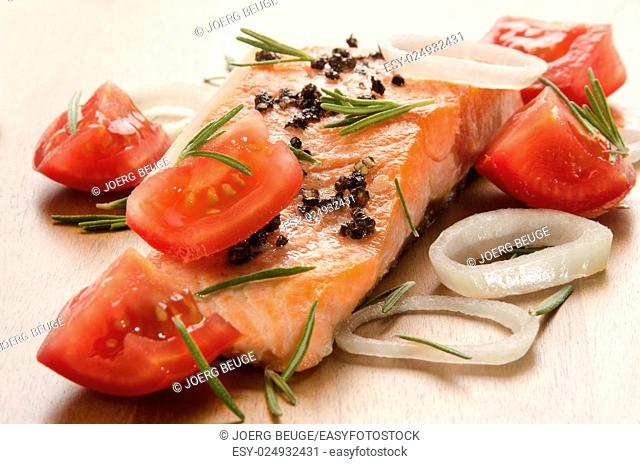 grilled salmon fillet with tomato cube, onion rings and rosemary on wood