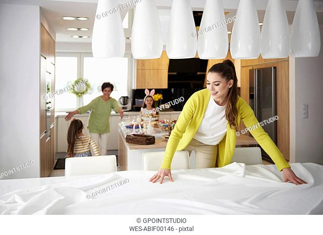 Smiling woman spreading the tablecloth at home with family in background